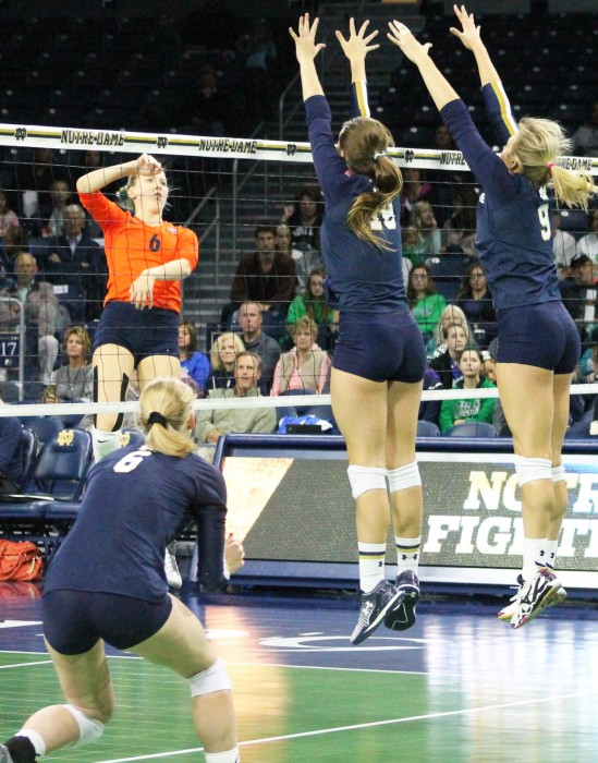 Irish middle blockers junior Katie Higgins, middle, and freshman Rebecca Nunge, right, attempt to block the ball during Notre Dame's 3-2 loss to Syracuse on Oct. 4 at Purcell Pavilion.