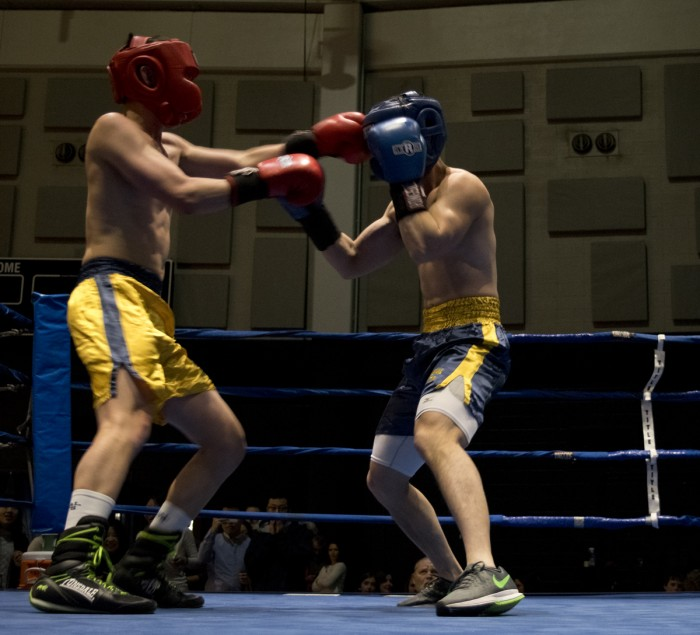 """Senior Liam """"Trooper"""" Chan, gold, lands a shot to the head of graduate student Qinfeng Wu during Bengal Bouts action Sunday at the JACC."""