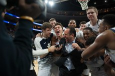 Irish players celebrate with head coach Mike Brey following Notre Dame's 61-56 win over Wisconsin on Friday night in Philadelphia.