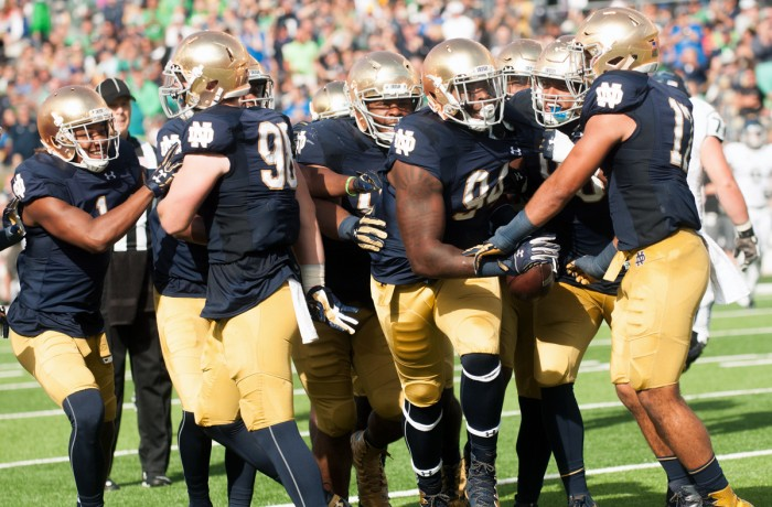 A gaggle of Notre Dame players celebrate an interception by senior defensive lineman Jarron Jones, center, in the second quarter of last weekend's 39-10 victory over Nevada at Notre Dame Stadium.