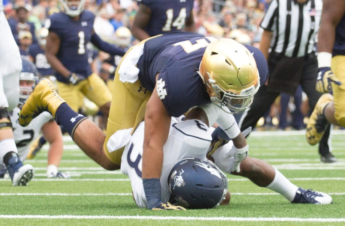 Senior linebacker and team captain James Onwualu finishes tackling Nevada sophomore receiver Ahki Mohammad in the backfield during Notre Dame's victory over the Wolf Pack last weekend. Onwualu finished the game with five tackles, tied for most on the team.