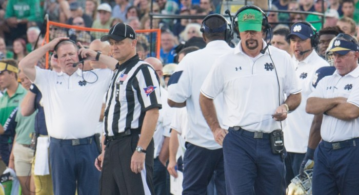 Former Irish defensive coordinator Brian VanGorder, green hat, watches his defense while head coach Brian Kelly