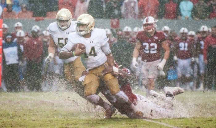 Irish junior quarterback DeShone Kizer is tackled by a North Carolina State defender in one of the puddles that formed at Carter-Finley Stadium as Hurricane Matthew soaked the Raleigh, North Carolina, area.