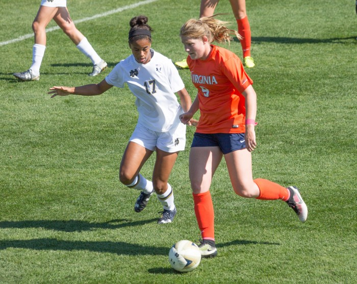 Senior midfielder Sandra Yu holds off a Virginia defender on Oct. 9. The Irish can share the ACC title with a win against Miami.