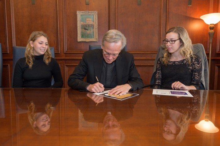 "University President Fr. John Jenkins signs the ""It's on Us"" pledge alongside student body vice president Becca Blais, left, and University policy liason Grace Watkins."