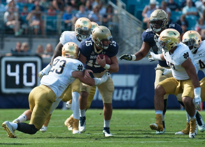 Notre Dame defenders tackle Navy quarterback Will Worth in Saturday's 28-27 loss to the Midshipmen in Jacksonville.