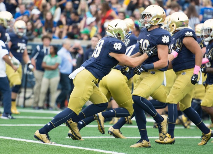 Irish senior running back Austin Ross warms up with a teammate before Notre Dame's victory over Miami on Oct. 29.