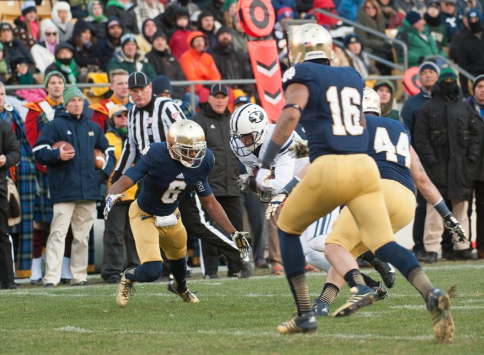 """Senior cornerback KeiVarae Russell, left, prepares to make a tackle during Notre Dame's 23-13 win over BYU at Notre Dame Stadium on Nov. 23, 2013. Russell was one of five players suspended in summer 2014 as part of the """"Frozen Five"""" scandal. Notre Dame was placed on probation by the NCAA and ordered to vacate wins from the 2012 and 2013 seasons Tuesday."""