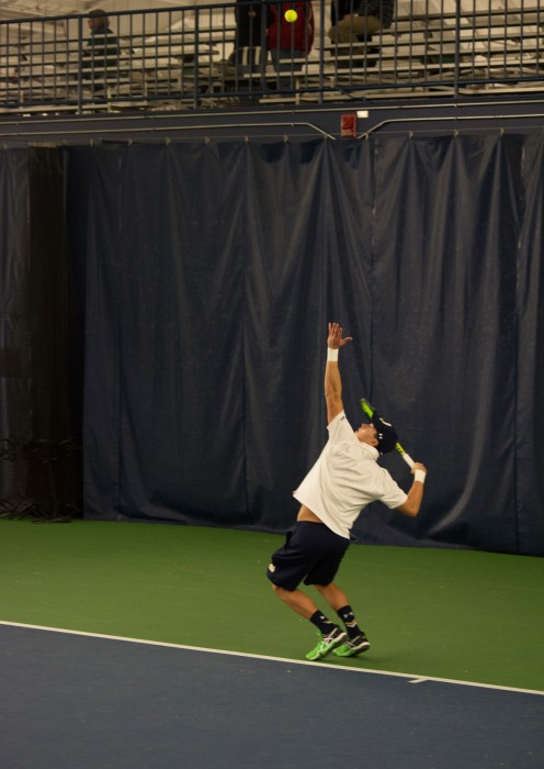 Irish junior Brendon Kempin tosses the ball for a serve during Notre Dame's 5-2 win over Indiana on Feb. 7 at Eck Tennis Pavilion. Kempin's doubles match went unfinished as the Irish won before it came to an end.