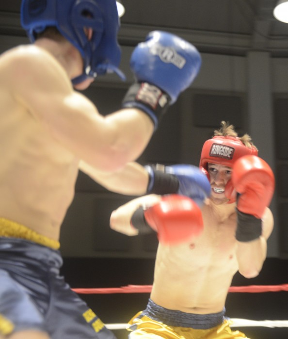 """Senior Chip Blood, in gold, fights against freshman Parker """"Zika"""" Revers in a 154 lb. weight division match in the Bengal Bouts tournament Tuesday night at the Joyce Center."""