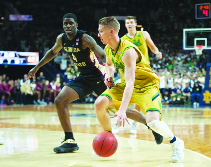 Irish sophomore guard Rex Pflueger dribbles past a Florida State defender during Notre Dame's 84-72 victory Feb. 11 at Purcell Pavilion. Mike Brey said Pflueger would retain his starting spot this weekend.