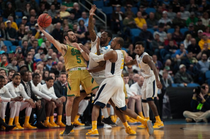 Irish junior guard Matt Farrell fends off two defenders during Notre Dame's 83-71 loss to West Virginia on Saturday at KeyBank Arena.
