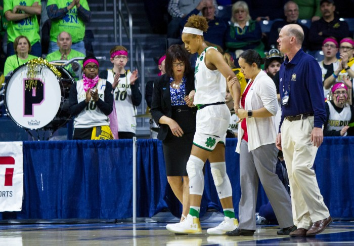 Irish junior forward Brianna Turner walks off the court and heads toward the locker room with assistance from team trainers during Notre Dame's 88-82 win over Purdue on Sunday at Purcell Pavilion.