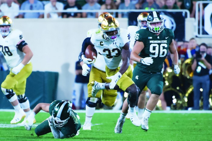 Irish junior running back Josh Adams dodges a Spartan defender during Notre Dame's 38-18 victory over Michigan State this past Saturday at Spartan Stadium in East Lansing, Michigan. Adams rushed for 57 yards in the game before leaving the game due to ankle stiffness.