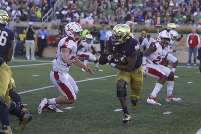 Irish junior running back Josh Adams dodges a defender during Notre Dame's 52-17 win over Miami (OH) on Saturday at Notre Dame Stadium.