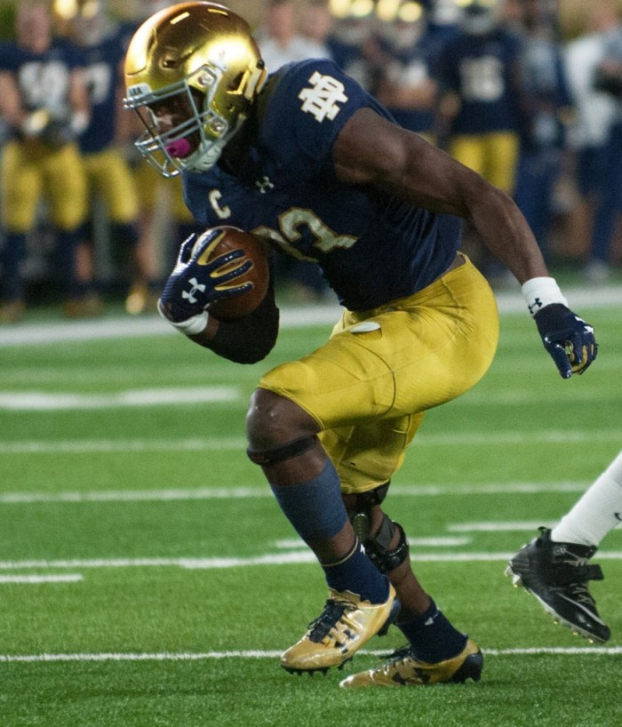 Irish junior running back Josh Adams looks downfield as he passes a defender during Notre Dame's 49-14 win over USC on Saturday at Notre Dame Stadium.