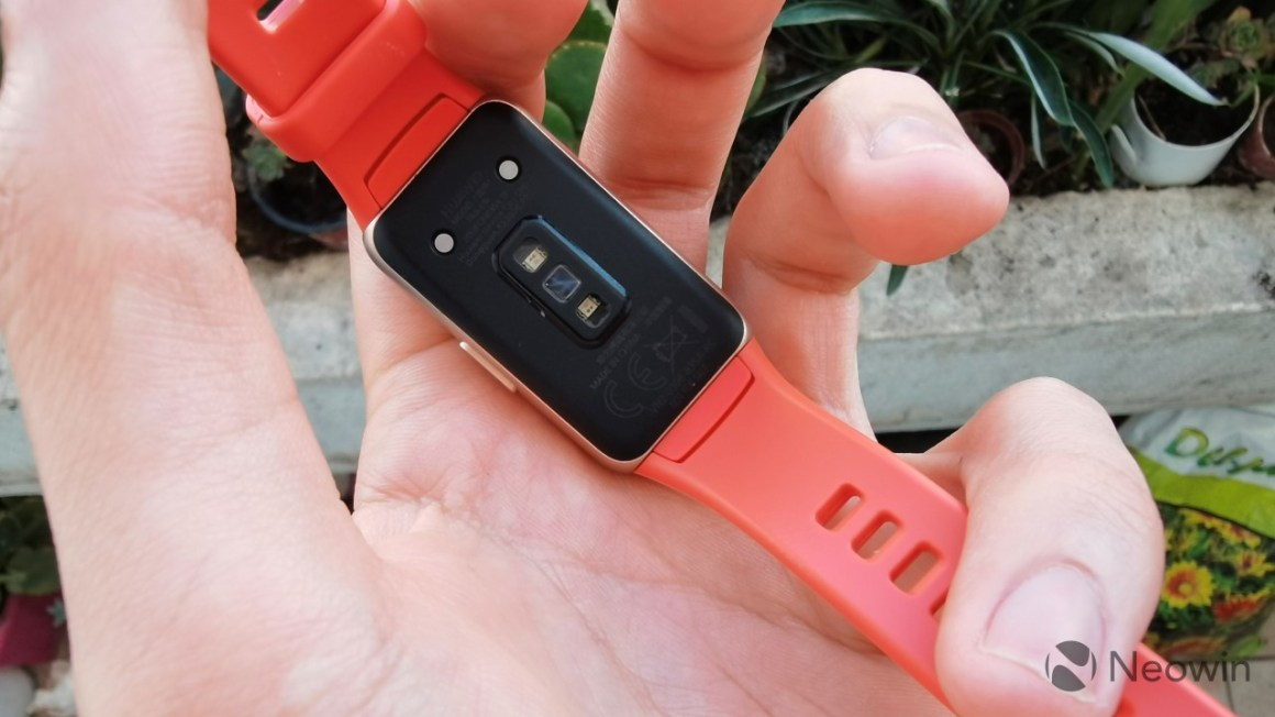 Huawei Band 6 resting face down on a hand showing the sensors on the back