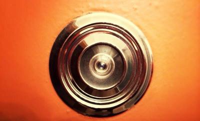 Ein türspion auf einer rot lackierten Tür ist zu sehen.