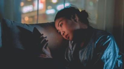 Person sitzt abends alleine zu Hause am Smartphone