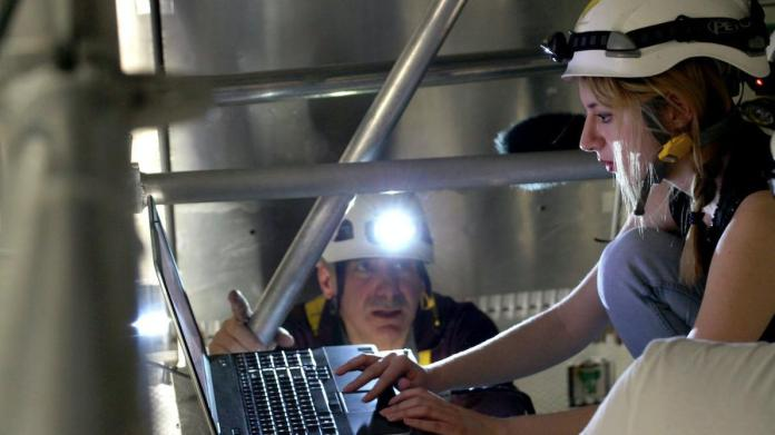Two scientists with safety hats and headlamps, one at a computer