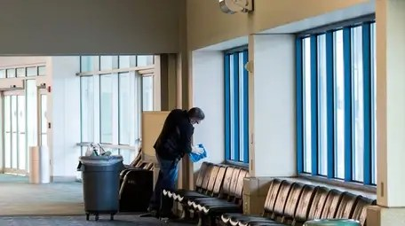 A worker cleans surfaces at Long Island MacArthur