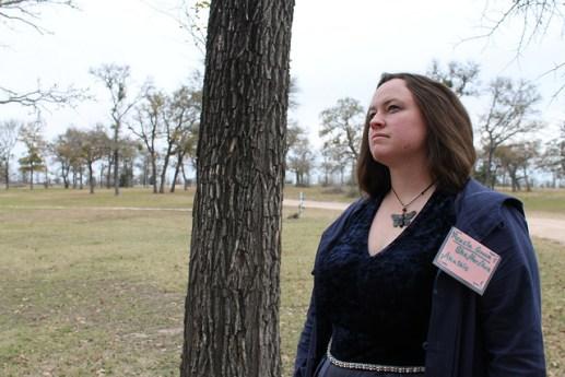 Woman in a cloak near a tree