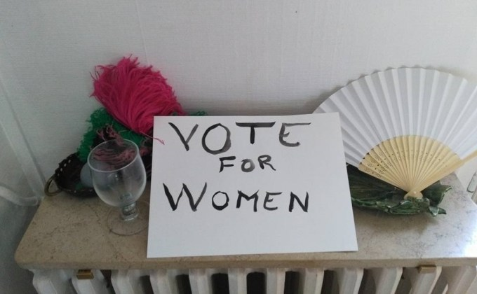 A sign that reads Vote for Women, a fan, a glass, and other props