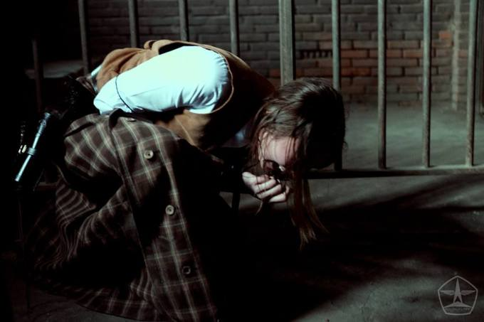 A woman in a jail cell and western clothing bent over and crying