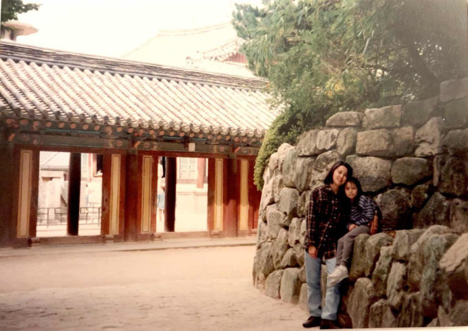 Photo of a mother her young girl posed against a rock wall with a building behind them