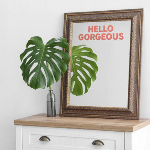 A gold framed mirror with a pink text quote saying 'Hello Gorgeous'