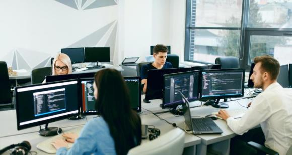 Group of people on computers around a table at work