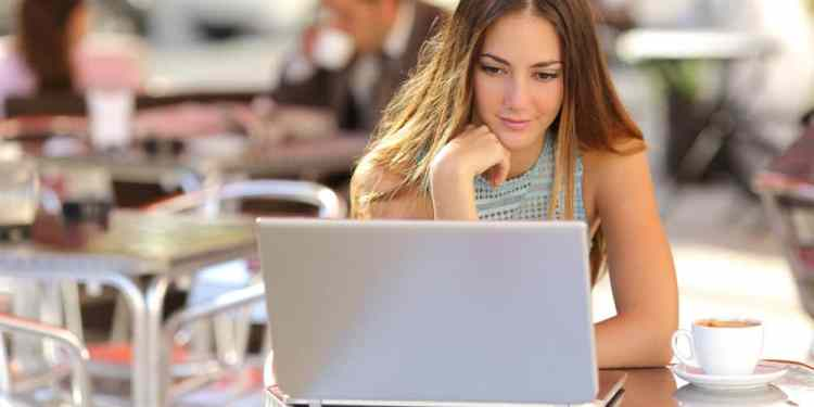 Attentive woman watching media in a laptop in a coffee shop with people in the background