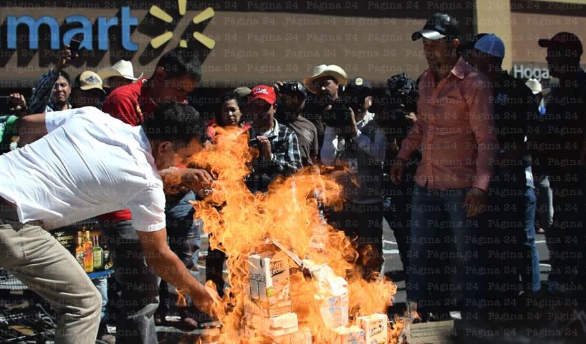 Afuera del Walmart de 16 de Septiembre, en el centro de la ciudad, cientos de productores de leche protestaron contra la falta de apoyo del gobierno estatal y federal; compraron lácteos y los apilaron para prenderles fuego, como forma de manifestación/Fotos: Rogelio Castro