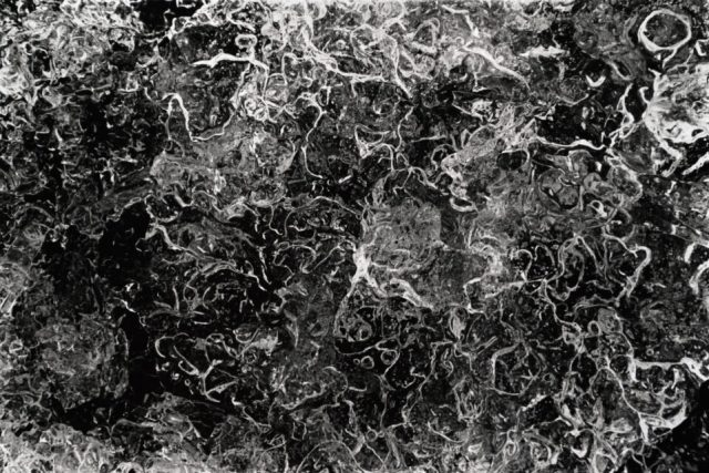 Snow and ice make great abstract macro photography subjects up close. This black and white photo shows bubbles in a piece of ice.
