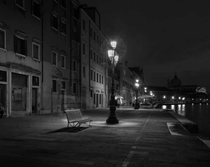 An empty bench and a characteristic 3 light lamppost.