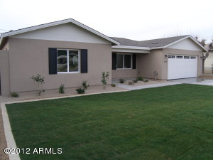 Front of home with large, grassy front yard.