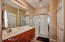 Master bathroom with large shower with sliding doors. Has private toilet room.