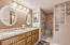 Beautiful Master Bathroom. Features granite countertops, double sinks, on demand hot water, a private toilet room and best of all THE SHOWER. The shower is a large walk-in w/ oversize travertine like tile on the walls & elegant travertine like mosaic on the floor with a coordinating wall detail.