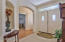 The entry is very welcoming and light with a glass transom above the double doors! A niche graces the entry wall to display your favorite decor! Lovely arches open to the den and guest bedroom (the archway shown), and the arch to the greatroom is where the photographer is standing.