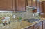 TILE BACKSPLASH COORDINATES BEAUTIFULLY WITH SLAB GRANITE COUNTERTOP & RICH WALNUT-STAINED CABINETS.