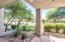 covered tiled patio and colorful desert landscape in private back patio overlooking golf course