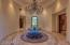 16 foot ceilings in rotunda foyer with crystal & rod iron chandelier.