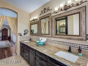 Master bathroom has travertine flooring, dual vanities with granite counters, gorgeaus framed mirrors, and new cabinetry with soft closing feature.