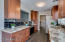 Kitchen features tiled backsplash, passthrough to living room and entry entry to laundry room.