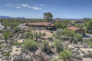 Natural desert landscaping offers privacy on this corner acre lot