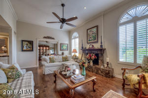 Living room with view into den, fireplace & plantation shutters.