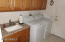 INSIDE LAUNDRY WITH UTILITY SINK W. VANITY STORAGE & GRANITE TOP.
