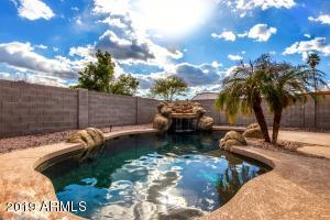 The custom PebbleTec pool with waterfall and grotto is perfect for AZ summers