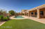 Low maintenance backyard with desert landscaping and faux grass.