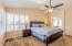 Spacious master suite with double door entry, vaulted ceilings and shutters.
